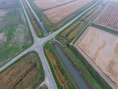 Crossroads paved roads through the fields. View from above Stock Photos