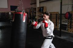 Man practicing karate with punching bag Kuvituskuvat