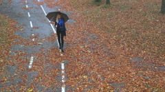Blond girl with umbrella walking down the street covered with dry leaves Stock Footage