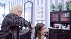 Hairdresser and client, a beautiful young girl in a beauty salon Stock Footage
