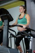 Pregnant woman exercising on elliptical machine Kuvituskuvat