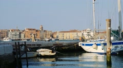 Venice, Italy, boats in harbour reflecting in calm waters of a canal Stock Footage