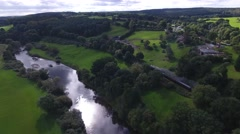 Aerial shot of a long steam train going through woodland beside a river. Stock Footage