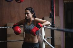 Tired female boxer in boxing gloves Stock Photos