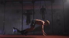 Athletic shirtless man doing backflip burpee at the gym Stock Footage