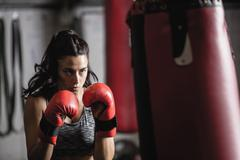 Female boxer practicing boxing with punching bag Stock Photos