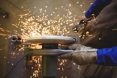 Welder cutting metal with electric tool in workshop Stock Photos
