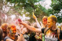 Young people having fun and dancing together at Holi color festival in park Kuvituskuvat