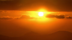 Vivid sunrise over silhouetted hills,bright red sun, timelapse. Stock Footage