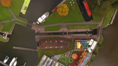 Birdseye aerial view of a fairground and canal lock area with boats. Stock Footage
