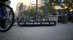 New York Sign With Bike Riders and Pedestrians Stock Footage