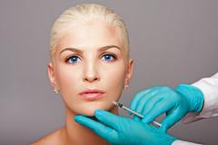 Cosmetic plastic surgeon injecting aesthetics face Stock Photos