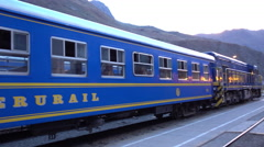 A blue train waits to depart at sunset in the mountains of Peru Stock Footage