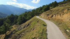 Aerial drone motion mountain road rural countryside hilly landscape sunny Stock Footage