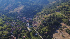 Aerial drone beautiful mountain village remote forest vegetation hilly terrain Stock Footage