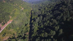 Aerial beautiful countryside landscape hilly green mountains forest power line Stock Footage