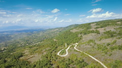 Aerial beautiful countryside hilly landscape wide mountains forest remote road Stock Footage