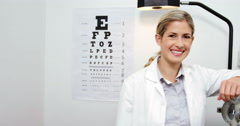 Beautiful optometrist standing in ophthalmology clinic Stock Footage