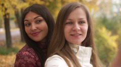 Two pretty girls walking in autumn park, make selfie, fooling around on camera Stock Footage
