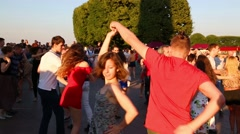 People dance to music on the Spit of Vasilyevsky Island in St. Petersburg Stock Footage