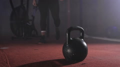 Close up of strong man in training suit going to the kettlebell and taking it Stock Footage