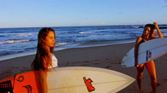 Two Surfers Dropping Boards On Sand With Sunshine In Background In Slow Motion Stock Footage