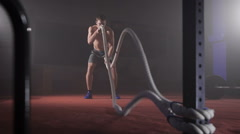 Cute muscular man doing crossfit rope double wave exercise at the gym Stock Footage