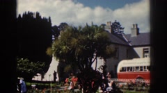 1961: people playing around in a garden area parked bus DUBLIN IRELAND Stock Footage