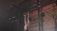Young man in a good shape doing muscle-ups exercises on the sport rings at the Stock Footage