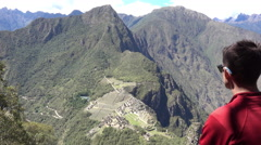 Man overlooking Machu Picchu from the top of the hike of Huayna Picchu Stock Footage
