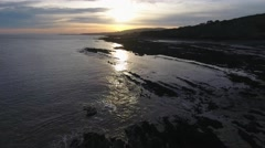 Slow low aerial view over a beach at sunrise. Stock Footage