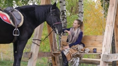 Girl on a swing with a black horse in the autumn Stock Footage