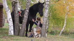 Girl sitting on a bench among the birch trees in the autumn with a horse Stock Footage