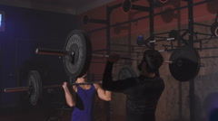 Two athletes at the same time lift the bar with weight Stock Footage