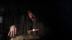 Necromancer casts spells from thick ancient book by candlelight, behind Stock Footage