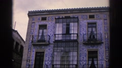 1966: a three storied building with four balconies and people walking Stock Footage