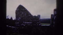 1961: two people taking a video near an iron fence like and old tower DUBLIN Stock Footage