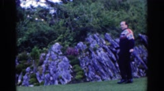 1961: a man posing before the camera framed by stones and a wooded area DUBLIN Stock Footage
