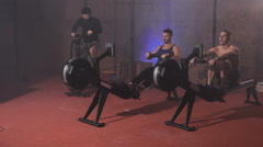 Front view of sportsmen doing cycling and rowing training at the gym Stock Footage