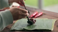 Woman placing rendang jerky beef stew on banana leaf Stock Footage