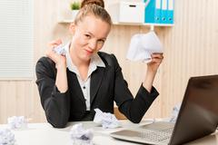 Angry and aggressive businesswoman crumples documents Stock Photos