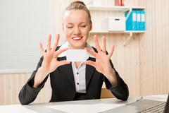 Business woman showing a small card for an inscription in the office Stock Photos