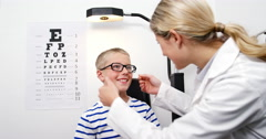 Optometrist giving high five to young patient Stock Footage