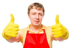 Happy man housewife in apron and gloves shows gesture Stock Photos