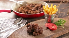 Rendang jerky beef stew on a cutting board served with french fried potatoes  Stock Footage