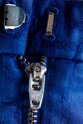 Fragment of blue jacket with metal zipper. ziplock background. Close up. Stock Photos