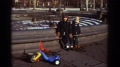 1971: two young boys sit on the outside edge of an empty water fountain  Stock Footage