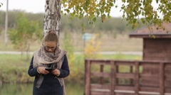 Woman using smart phone typing message outdoor Stock Footage