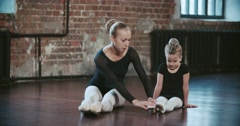 Adult and the little ballerinas are doing joint stretching training Stock Footage