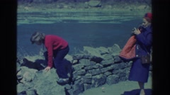 1971: girl climbs onto stone wall by river  Stock Footage